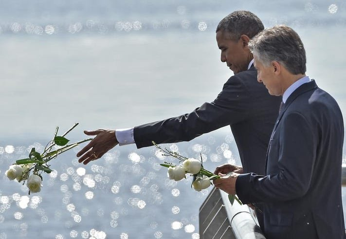 U.S. President Barack Obama and Argentinian President Mauricio Macri throw a bouquet of white flowers into the River Plate in Buenos Aires on March 24. (AFP PHOTO / NICHOLAS KAMM)