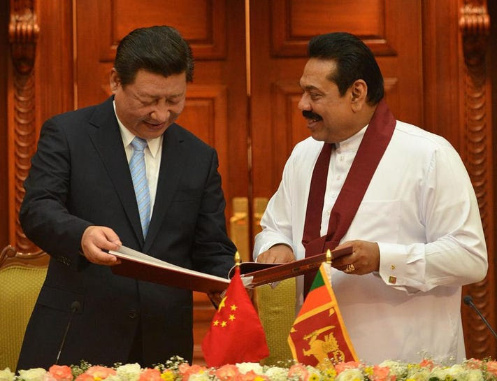 China's President Xi Jinping speaks with Mahinda Rajapaksa